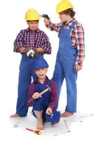 blaue Arbeitshosen, karierte Hemden und Bauhelme