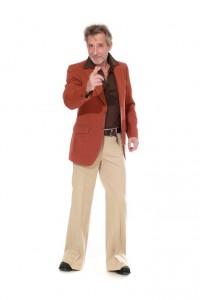 rostfarbenes Sakko mit hellen Steppnähten, beige Schlaghose, braunes Polohemd