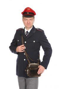 blaue Uniformjacke, graue Hose und Schaffnertasche und Mütze